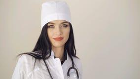 Sguardo felice di medico abbastanza femminile che guarda alla macchina fotografica su fondo 4K video d archivio