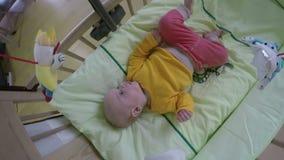 Sguardo interessato sveglio del bambino al giocattolo del carosello 4K video d archivio