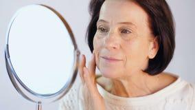 Sguardo invecchiato della donna alla sua pelle stock footage