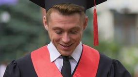 Sguardo laureato sorpreso del maschio giù con il sorriso sul fronte, opportunità di carriera video d archivio