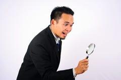 Sguardo molto felice asiatico dell'uomo d'affari tramite una lente d'ingrandimento isolata su bianco Fotografia Stock
