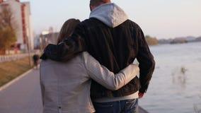 Sguardo posteriore delle passeggiate delle coppie negli abbracci giù la via video d archivio