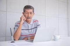 Sguardo senior dell'uomo d'affari dell'Asia al computer portatile ed al pensiero immagini stock libere da diritti