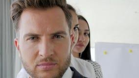 Sguardo serio del capo con i collaboratori, fronte dell'affare, ritratto degli uomini d'affari che stanno nella fila in ufficio, video d archivio
