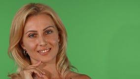 Sguardo sorridente della bella donna matura sbalorditiva meditatamente alla macchina fotografica fotografia stock libera da diritti