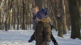 Sguardo sveglio del ragazzino ai suoi fratelli che giocano le palle di neve stock footage