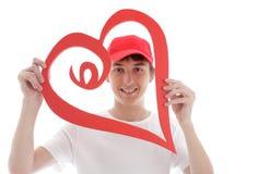 Sguardo teenager attraverso un cuore rosso di amore fotografia stock libera da diritti