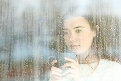 Sguardo teenager desiderante attraverso una finestra da solo Fotografia Stock