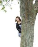 Sguardo teenager intorno all'albero Fotografia Stock