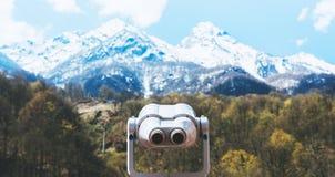 Sguardo turistico del telescopio alla citt? con le montagne della neve di vista, metallo binoculare sul punto di vista del fondo  fotografia stock
