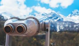Sguardo turistico del telescopio alla citt? con le montagne della neve di vista, metallo binoculare sul punto di vista del fondo  immagini stock