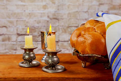 Shabbat candles in glass candlesticks with blurred covered challah Stock Photography