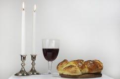 Shabbat Celebration. Eye level shot of the items used for Shabbat, candlesticks, lit candles,Challah,glass of wine Stock Image