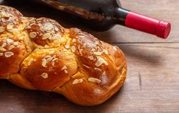 Challah bread with a bottle of red wine on wooden table. Shabbat concept, challah bread with a bottle of red wine on wooden table, view from above stock photography