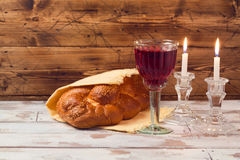 Shabbat concept with wine glass and challah bread on wooden table Royalty Free Stock Images