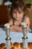 Shabbat eve. Jewish girl looks at lit sabbath candles before shabbat eve dinner Royalty Free Stock Images