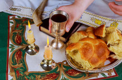 Shabbat eve table with uncovered challah bread, Sabbath candles. And Kiddush wine cup Stock Image