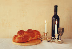 Shabbat image. challah bread, shabbat wine and candelas on wooden table. vintage filtered image