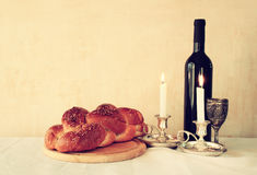 Shabbat image. challah bread, shabbat wine and candelas on wooden table. vintage filtered image.  Stock Photo