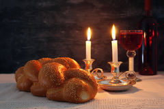 Shabbat image. challah bread, shabbat wine and candles. Low key shabbat image. challah bread, shabbat wine and candles on wooden table Stock Photo