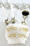 Shabbat - Jewish Holiday. Shabbat eve table with covered challah bread, candles and cup of wine Royalty Free Stock Images