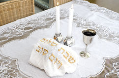 Shabbat - Jewish Holiday. Shabbat eve table with covered challah bread, candles and cup of wine Royalty Free Stock Image