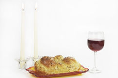 Shabbat Observance. All the necessary items to celebrate Shabbat includes Challah, or egg bread, glass of wine, two lit candles in candlesticks Stock Photography