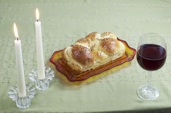 Shabbat Observance. All the necessary items to celebrate Shabbat includes Challah, or egg bread, glass of wine, two lit candles in candlesticks Stock Photo