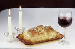 Shabbat Observance. All the necessary items to celebrate Shabbat includes Challah, or egg bread, glass of wine, two lit candles in candlesticks Royalty Free Stock Photos