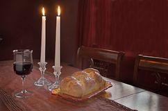 Shabbat Observance At Sunset: Challah, Glass of Wine, Two Lit Candles. All the elements used for Shabbat on the eve of The day of rest. Jewish observance Royalty Free Stock Image