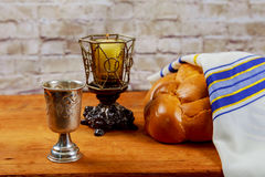 Shabbat or Sabbath kiddush ceremony composition with red kosher wine. And a traditional sweet fresh loaf of challah bread on a vintage wood background with Stock Photos