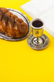 Shabbat Shalom, challah with glass of wine and book, on yellow background. Not isolated, copy space, author processing. Royalty Free Stock Photo