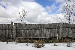 Shabby αγροτικός ξύλινος φράκτης από τους πίνακες στο χωριό στο χειμώνα και Στοκ Φωτογραφία