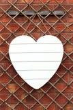 Shabby κομψή άσπρη καρδιά ενάντια στο τουβλότοιχο Στοκ Εικόνες