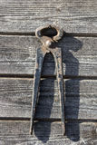 Shabby σκουριασμένες πένσες μετάλλων με τις κόκκινες λαβές που κρεμούν ξύλινο boa Στοκ Φωτογραφίες