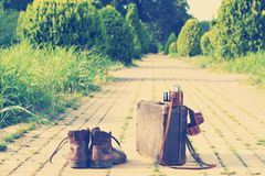 Ankle boots, cardboard suitcase, film camera, brick road. Post-processed. Royalty Free Stock Photography