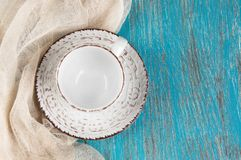 Shabby beige cup and saucer. On blue wooden shabby background. Top view and copy space for text Royalty Free Stock Photos