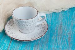 Shabby beige cup and saucer. On blue wooden shabby background. Copy space for text Stock Photos