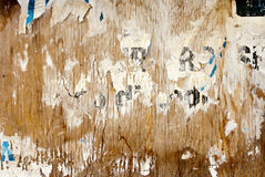 Shabby billboard. Fragments of torn poster glued on wooden panel Stock Image