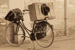 Shabby black hat and suitcases on the bike. Retro-styled and sepia toned image Stock Photo