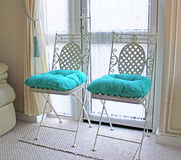 Shabby Chic. This photo shows two shabby chic chairs dresses with Aqua Blue cushions royalty free stock photo