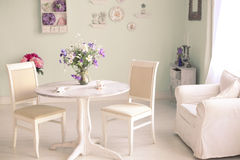 Shabby chic dining room interior with flowers decorative plates Stock Photo