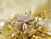 Shabby chic gift box nestled in gold Christmas garland. With bokeh lights background Stock Photo