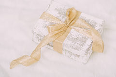 Shabby chic gift with golden ribbon on white  background Stock Photo