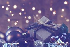 Shabby chic gift nestled in Christmas decorations with bokeh lig. Hts background Stock Image