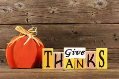 Rustic Give Thanks wood sign and pumpkin. Shabby chic Give Thanks wood sign and pumpkin against a rustic wooden background Stock Photography