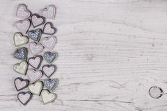 Shabby chic grey wooden background with a collection of hearts o