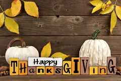 Shabby chic Happy Thanksgiving wood sign with pumpkin decor against wood. Happy Thanksgiving wood sign with white pumpkins and leaves against a rustic wooden Royalty Free Stock Photo
