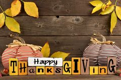 Shabby chic Happy Thanksgiving wood sign with pumpkin decor against wood. Happy Thanksgiving wood sign with cloth pumpkins and leaves against a rustic wooden Stock Images