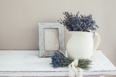 Shabby chic interior decor. For farmhouse. Lavender in pitcher and blank photo frame on a vintage shelf over pastel wall. Provence home decoration royalty free stock photography